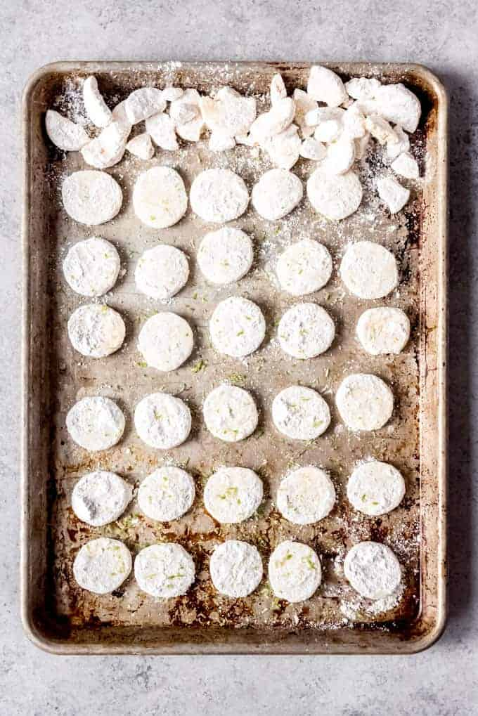 An image of lime meltaway cookies on a baking sheet right after being tossed with powdered sugar.