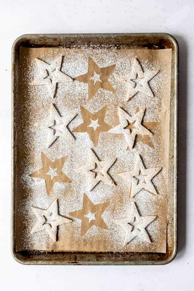 An image of the tops of linzer cookies shaped like stars and dusted with powdered sugar.