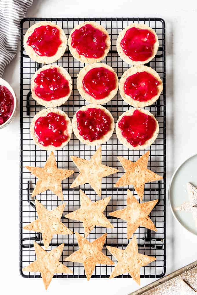 An image of linzer cookie halves being filled with raspberry preserves.