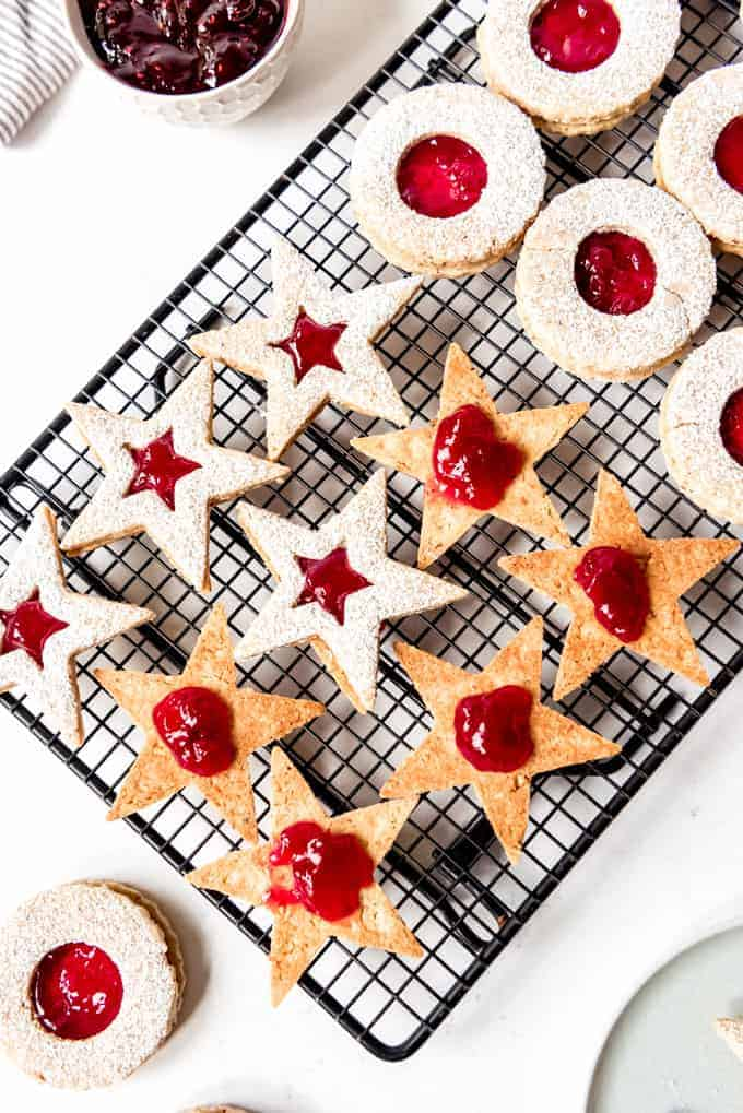 An image showing how to fill star-shaped linzer cookies with fruit preserves.