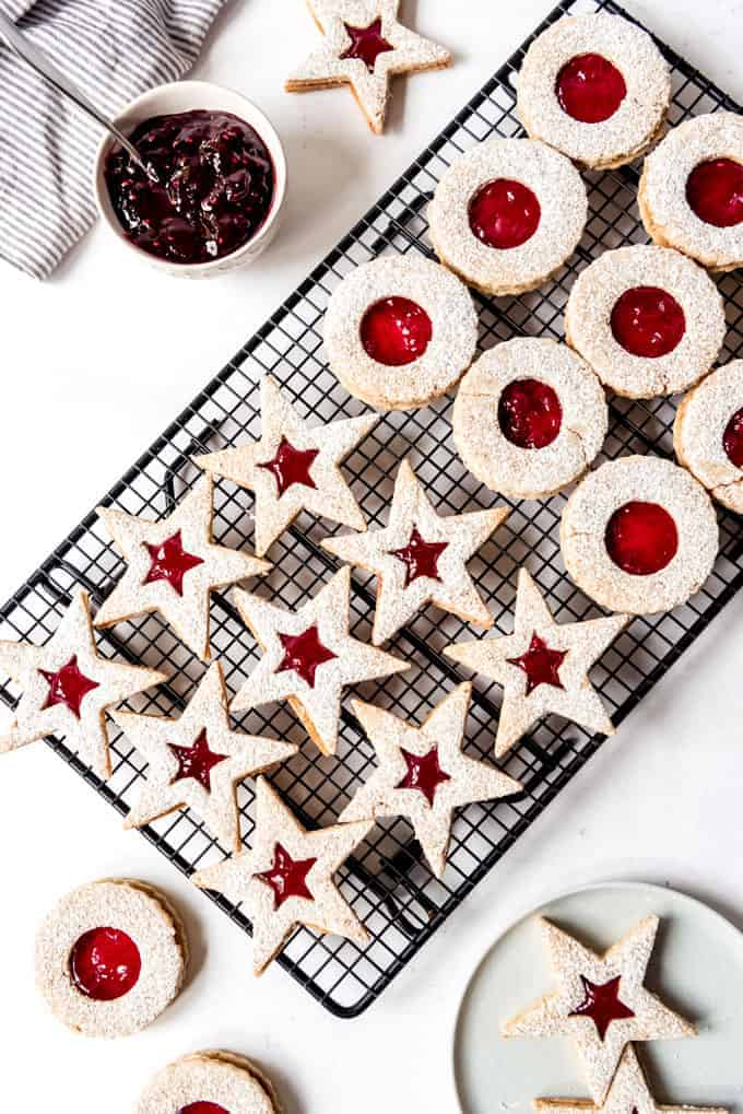 An image of homemade linzer cookies filled with raspberry and lingonberry preserves.