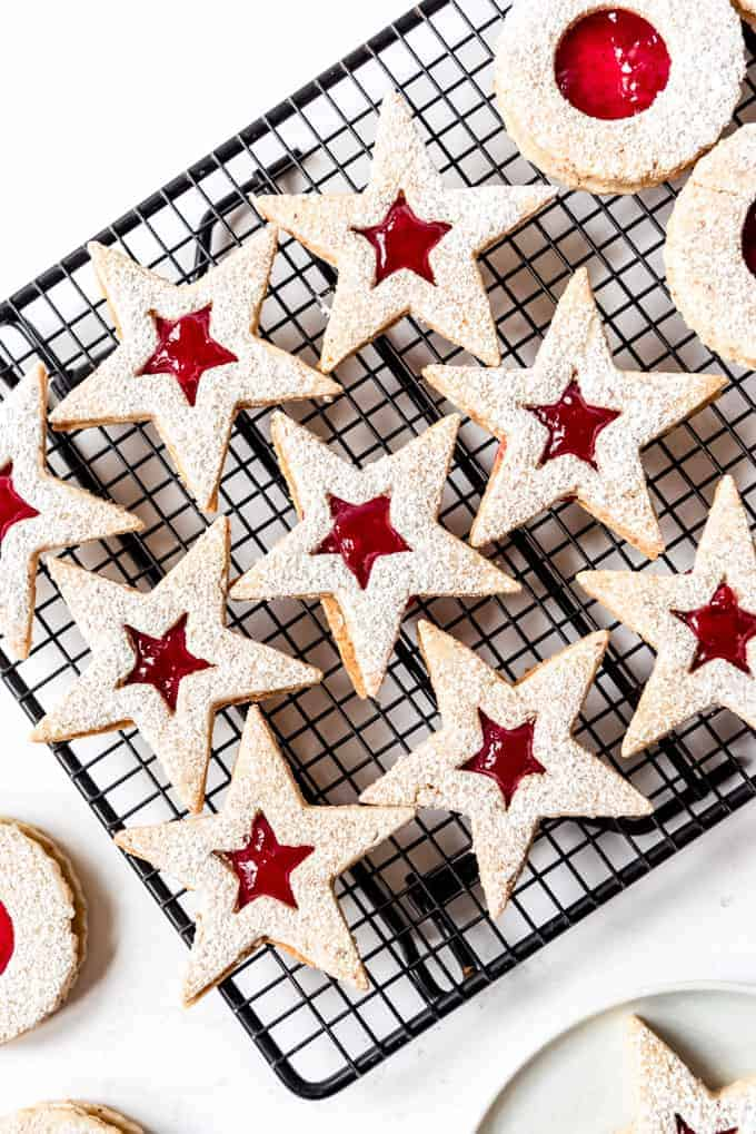 An image of star-shaped linzer cookies filled with fruit preserves.