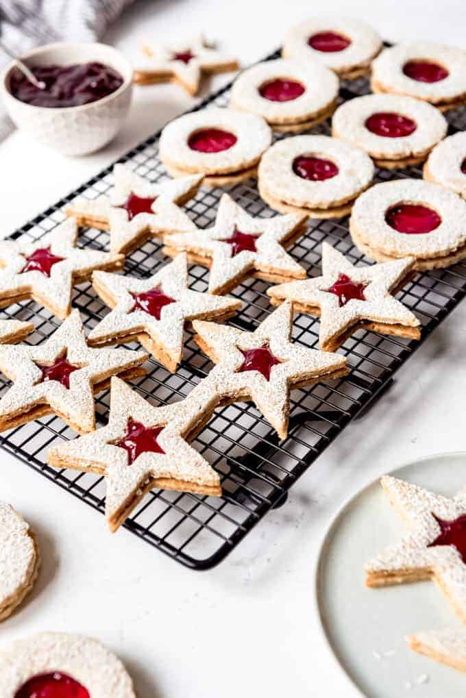 An image of star and circle shaped Linzer cookies filled with raspberry preserves on a wire rack.