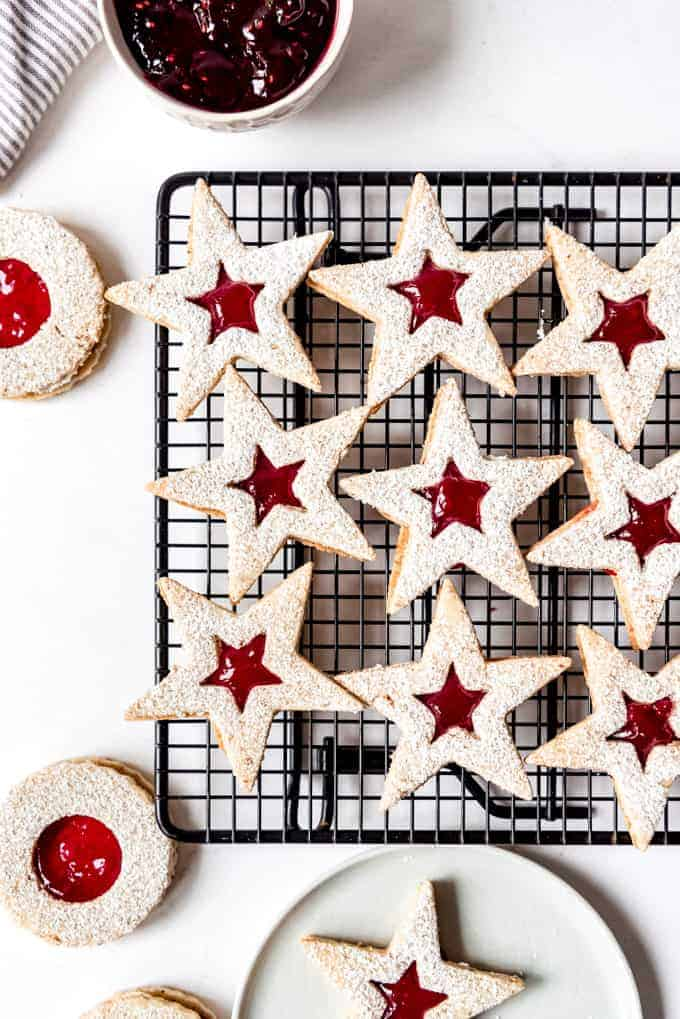 An image of Austrian linzer cookies shaped like stars on a wire cooling rack.