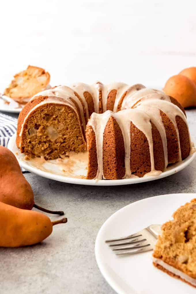 An image of a holiday bundt cake on a cake plate with glaze on it.