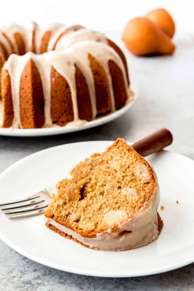 An image of a slice of pear ginger bundt cake on a white plate.