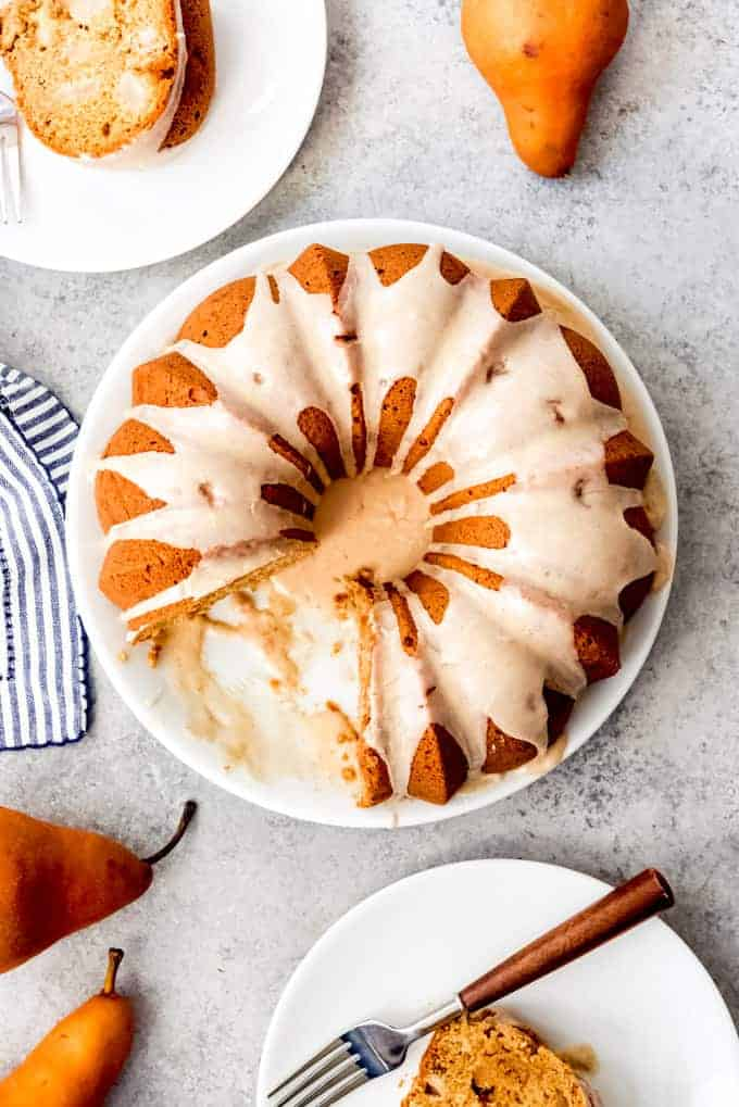 An image of a glazed pear ginger bundt cake with slices removed from it and served on white plates.