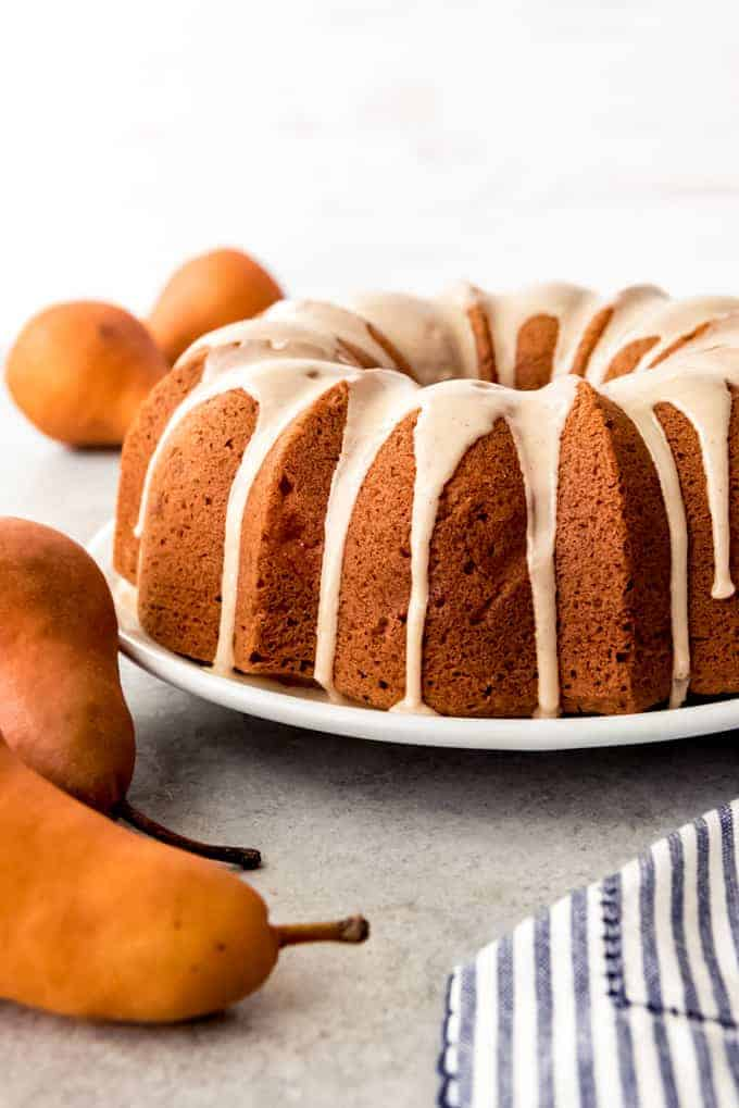 An image of a pear ginger bundt cake with a pear glaze dripping down the sides.