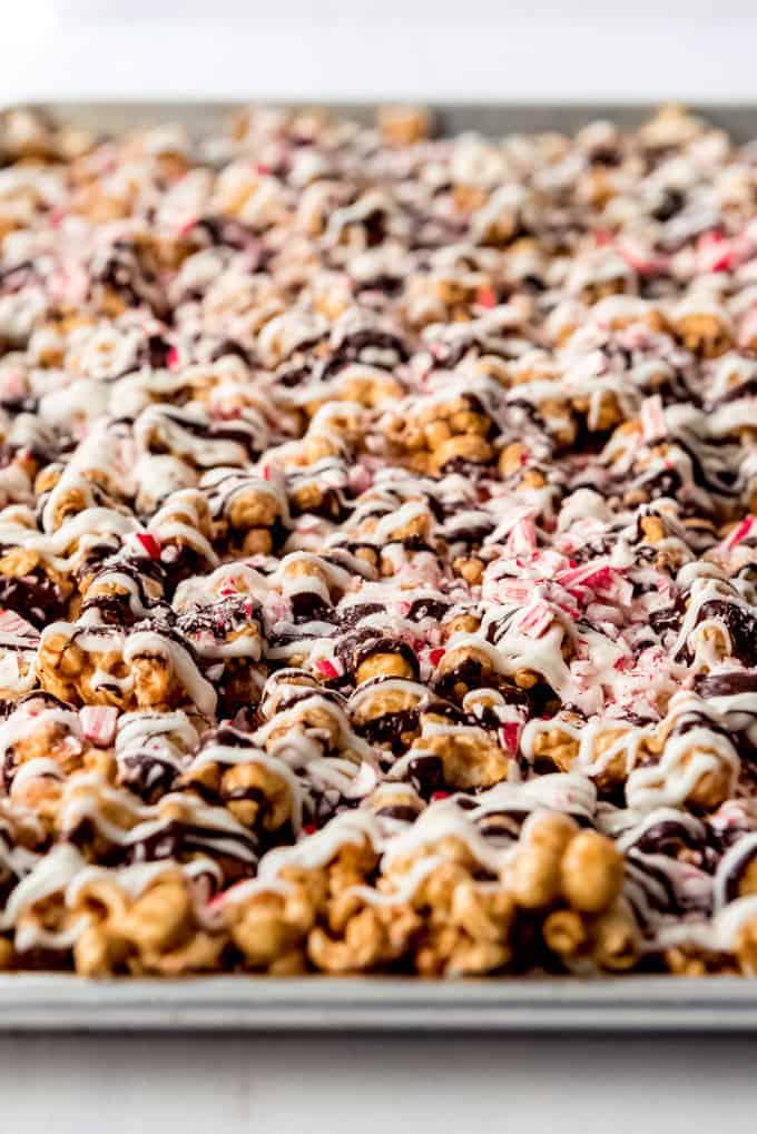 An image of peppermint bark caramel corn on a baking sheet.
