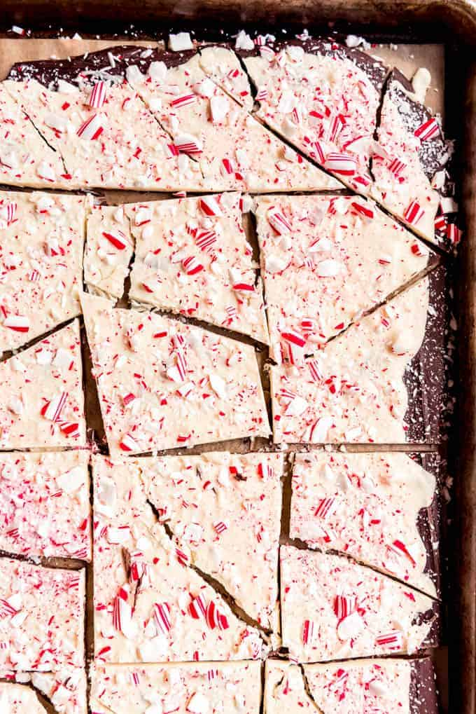 An image of broken up chunks of peppermint bark on a baking sheet.