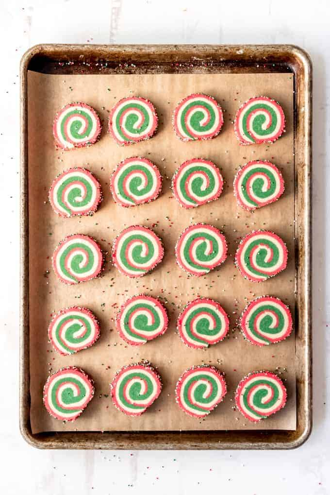 An image of slice-and-bake pinwheel cookies on a baking sheet lined with parchment paper.