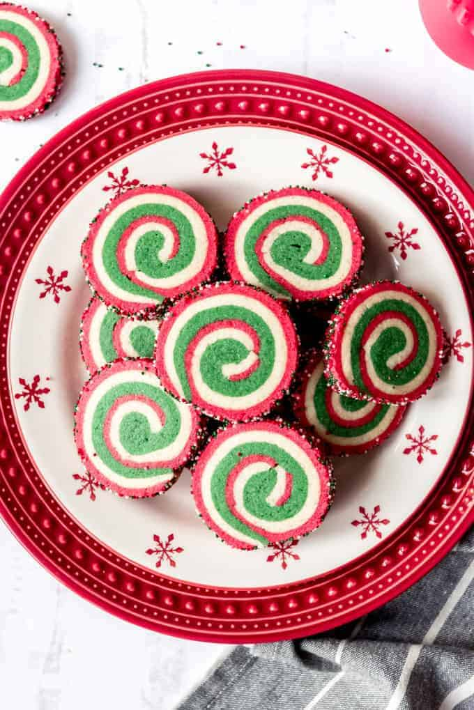 An image of Christmas pinwheel cookies on a festive red and white holiday plate.