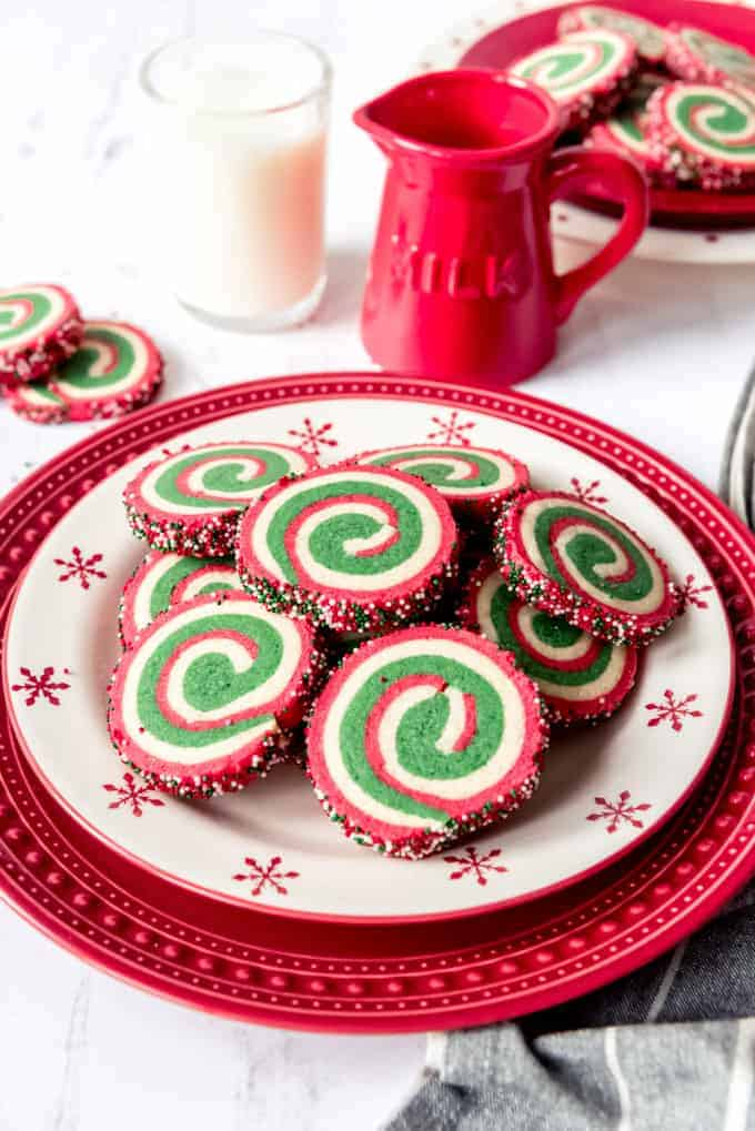 An image of Christmas pinwheel cookies on a plate with a glass of milk.
