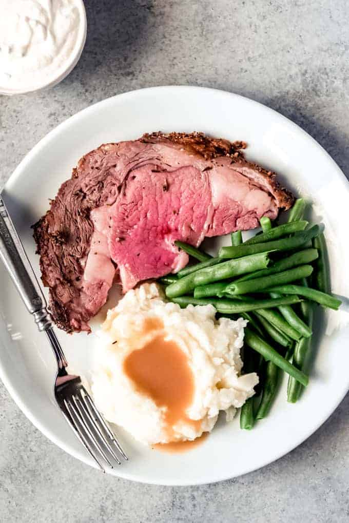 overhead shot of white plate with slice of prime rib, green beans, and mashed potatoes, horseradish sauce to the side