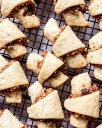 An image of cinnamon walnut rugelach on a wire cooling rack.