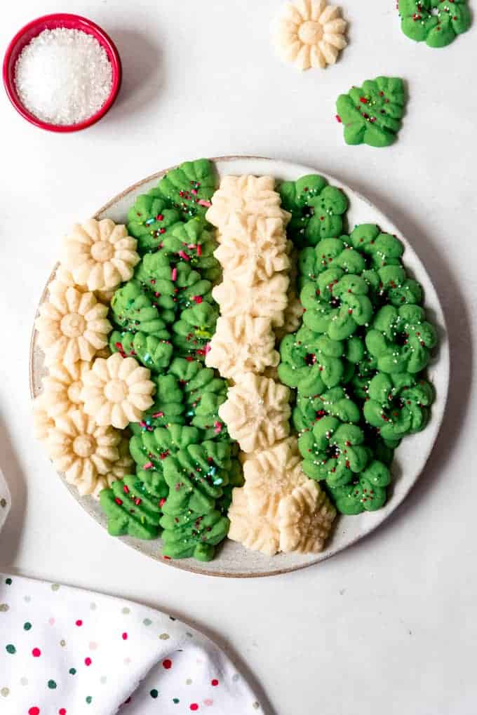 An image of a large plate filled with different designs of spritz cookies in green and white.