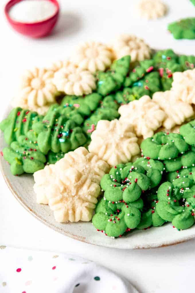 An image of classic Spritz cookies piled on a plate together.