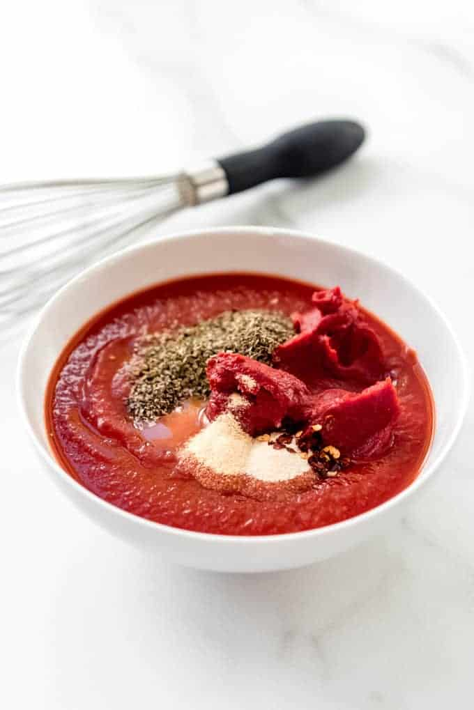 An image of a bowl of ingredients like tomato sauce, tomato paste, and herbs and spices for making homemade pizza sauce.