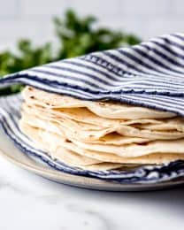 An image of homemade flour tortillas wrapped in a towel to stay soft.