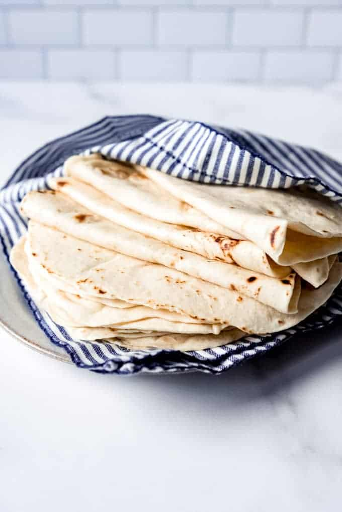 An image of a stack of fresh tortillas on a plate.