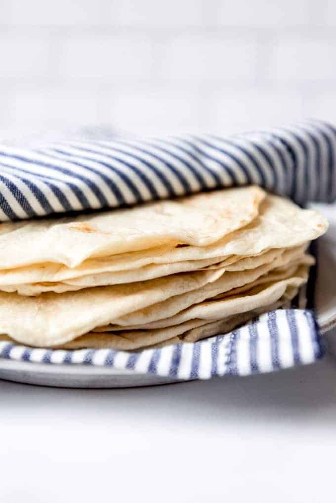 An image of soft homemade flour tortillas in stack on a plate.