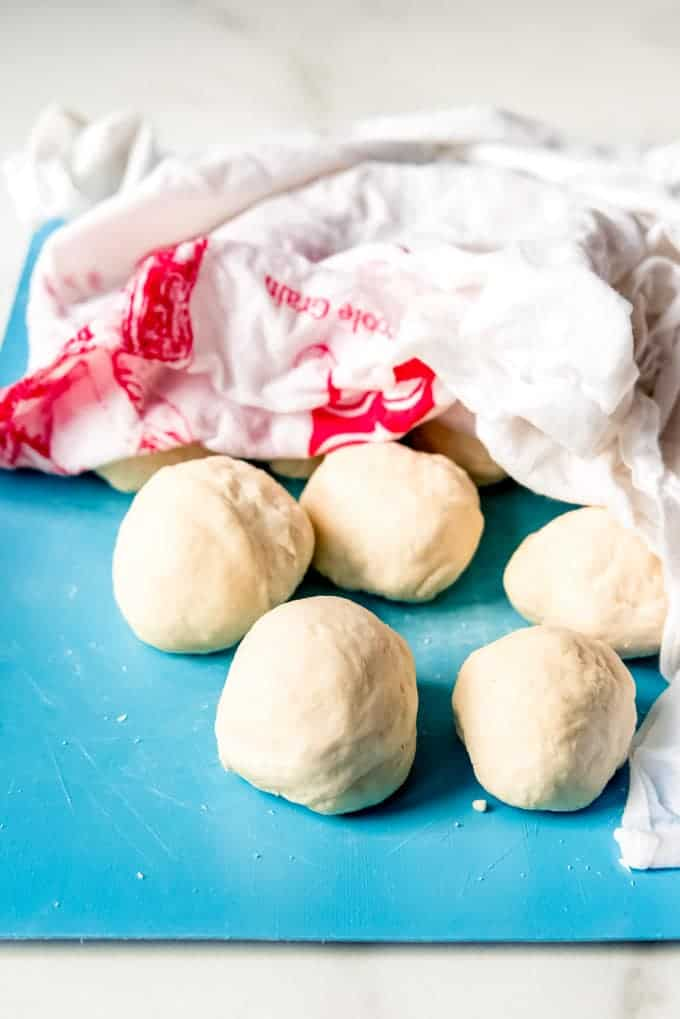 An image of balls of tortilla dough covered with a damp cloth.