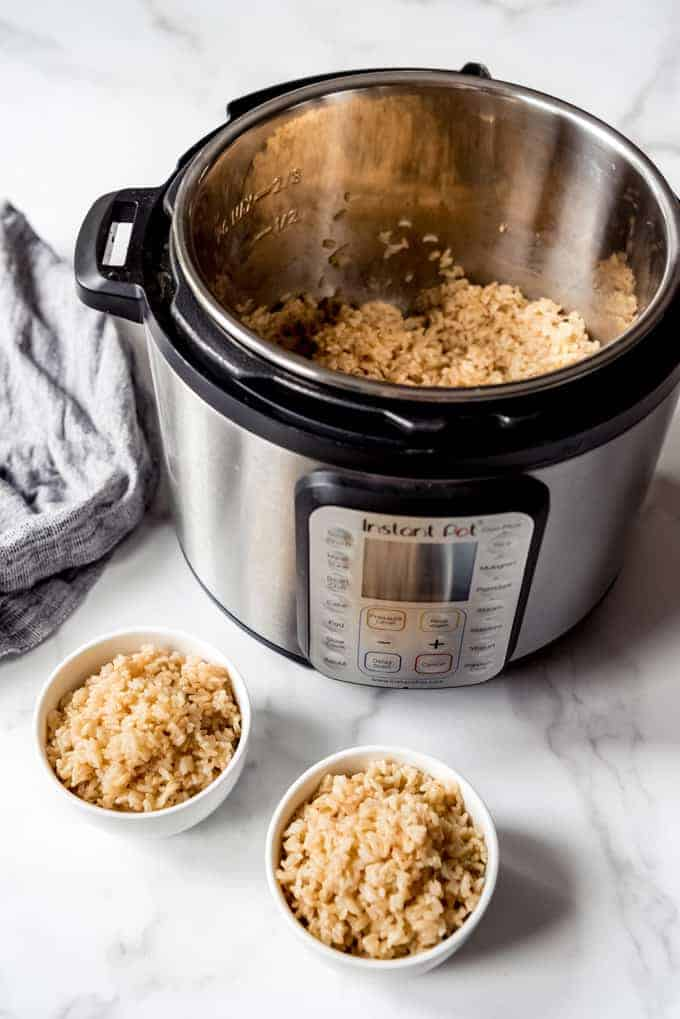 An image of bowls of healthy brown rice in front of an Instant Pot pressure cooker.