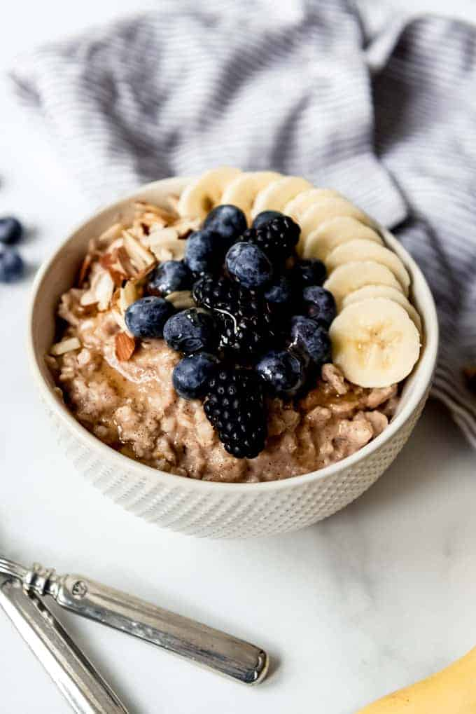 An image of a bowl of oatmeal with fresh fruit and nuts.