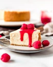 An image of a slice of Instant Pot Cheesecake topped with raspberry sauce.