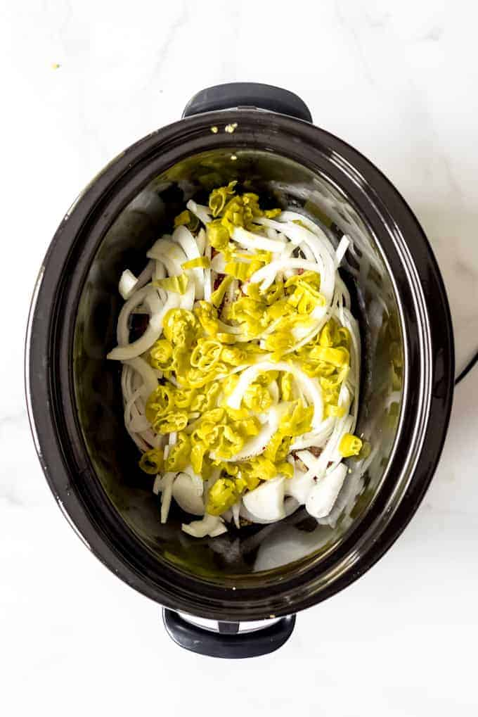 An image of a slow cooker filled with onions and pepperoncinis to make Italian beef.