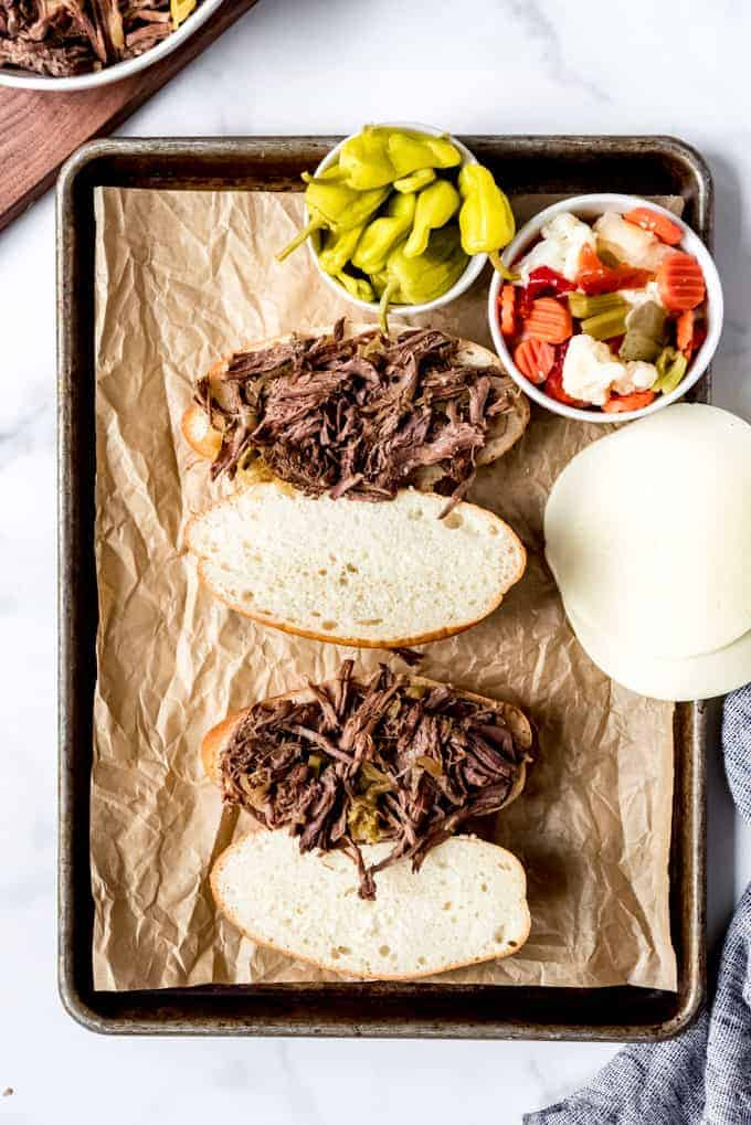 An image showing how to assemble Italian beef sandwiches with pepperoncini and giardiniera.