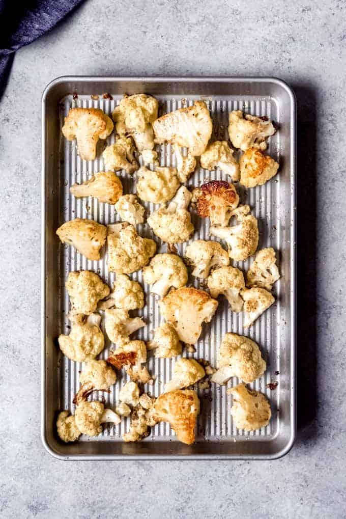 An image of roasted cauliflower on a baking sheet.