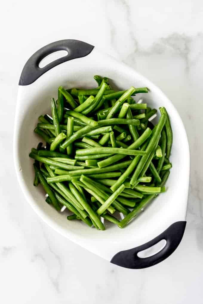 An image of washed and prepped green beans in a colander.