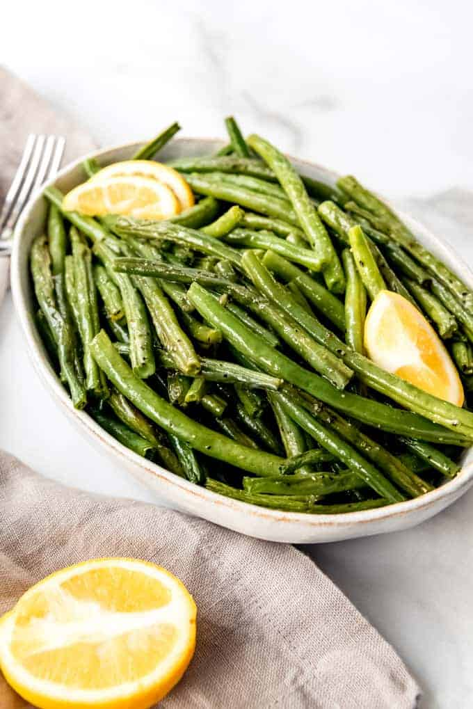 An image of simple, healthy green beans in a serving bowl with lemon slices.