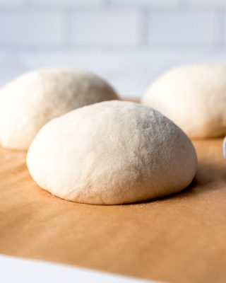 An image of balls of homemade pizza dough on parchment paper.