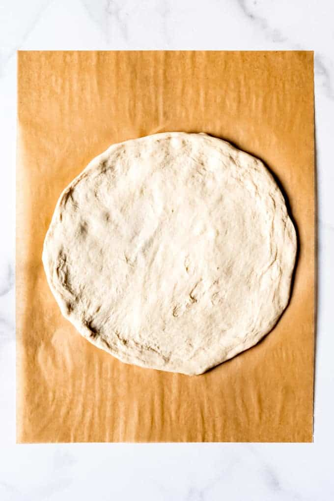 An image of a circle of unbaked pizza dough.