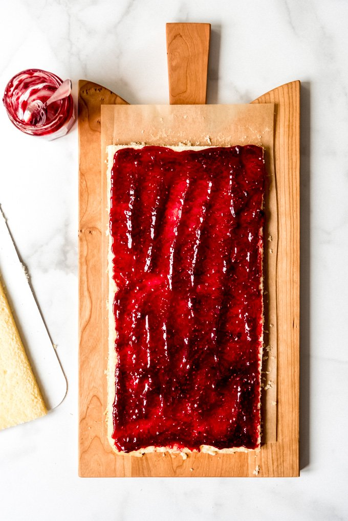 An image of white cake with raspberry jam spread on it for a filling.