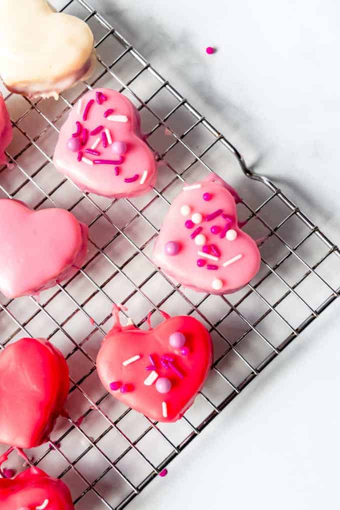 An image of heart-shaped mini cakes covered in glaze and sprinkles.