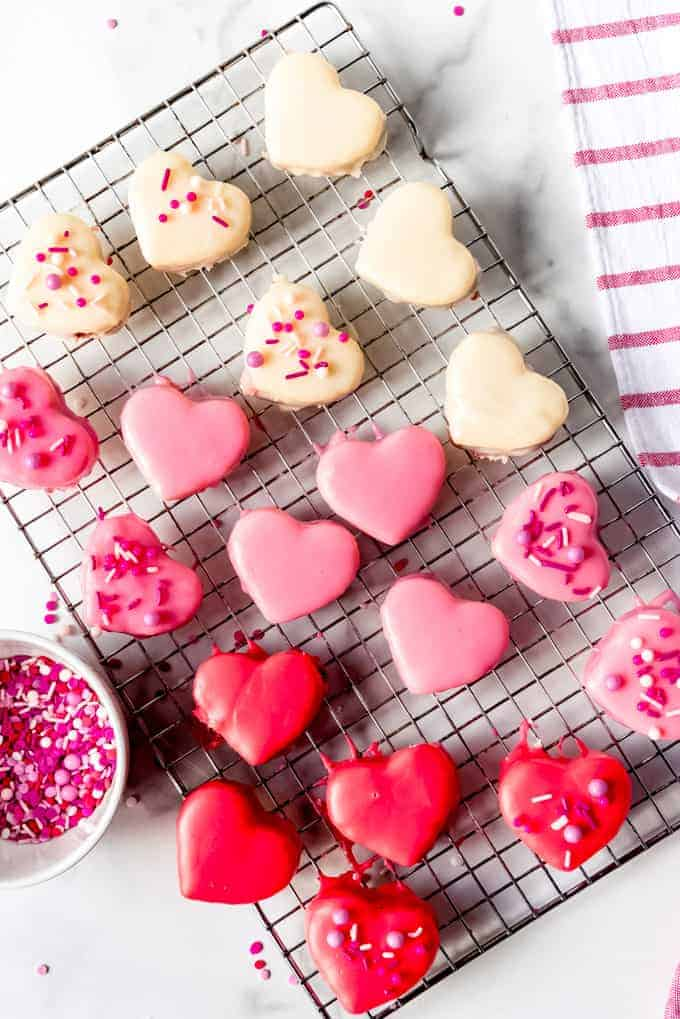 An image of heart-shaped Valentine's Day petit fours covered in red, white, and pink icing.