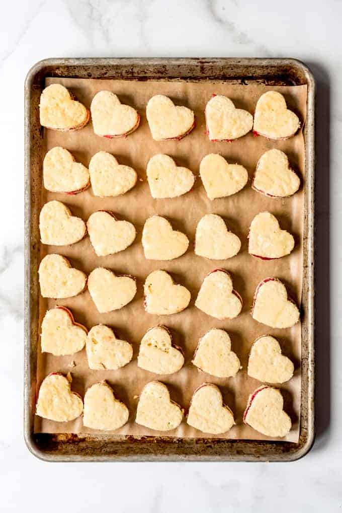 An image of small heart-shaped cakes on a baking sheet.
