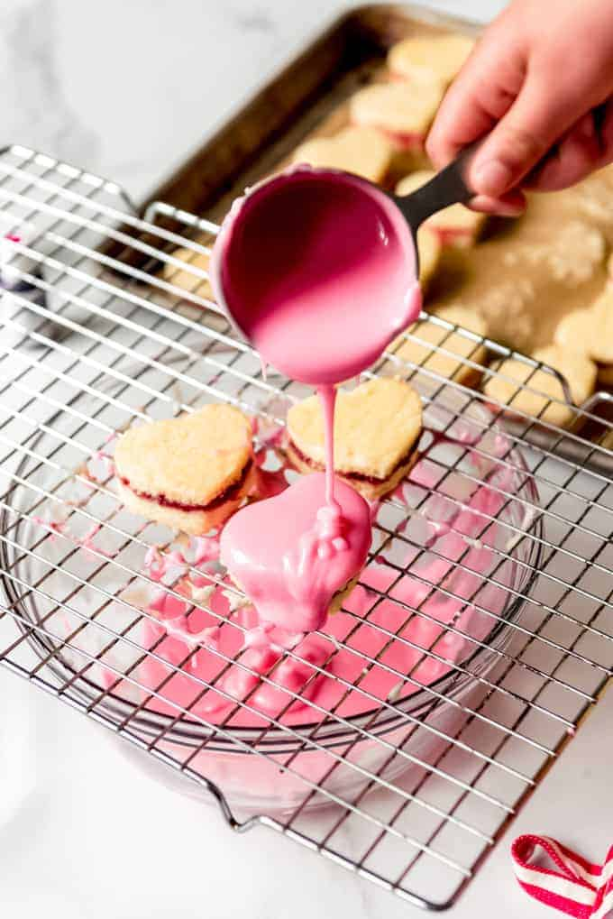 An image of pink glaze being poured over tiny heart-shaped cakes.