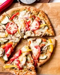 An image of a whole wheat pizza topped with fresh veggies, pesto, and cheese.