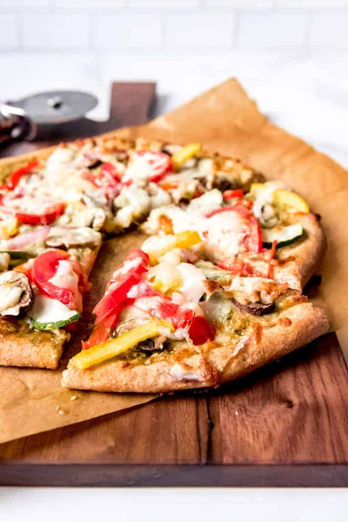 An image of a slice of whole wheat veggie pizza on a cutting board.