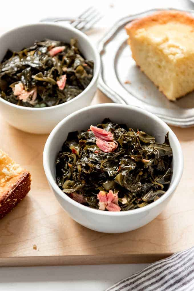 An image of Southern collard greens cooked with ham hock next to a slice of cornbread.