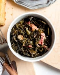 An image of a bowl of slow cooked greens with bits of smoky ham hock.