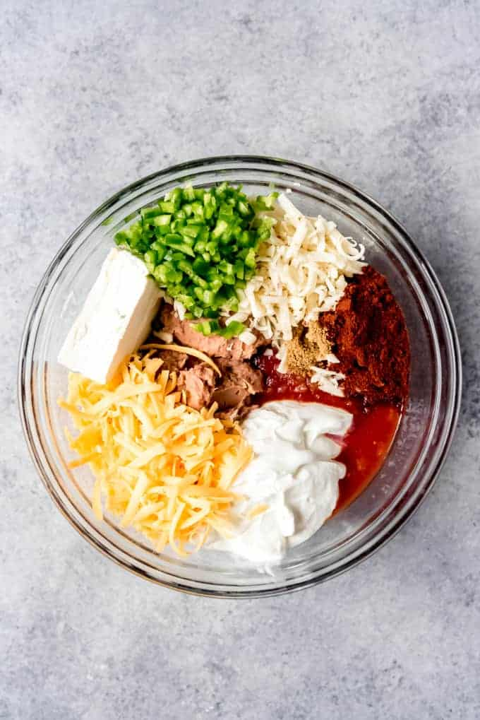 An image of the ingredients for refried bean dip in a glass bowl.