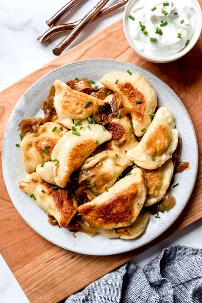 An image of homemade pierogies on a plate with chives and sour cream.