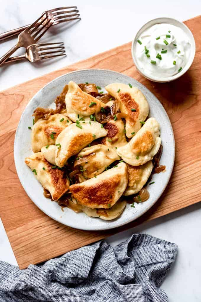 An image of homemade polish dumplings with sour cream on the side.