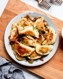 An overhead visual of a plate filled with crispy golden pierogi