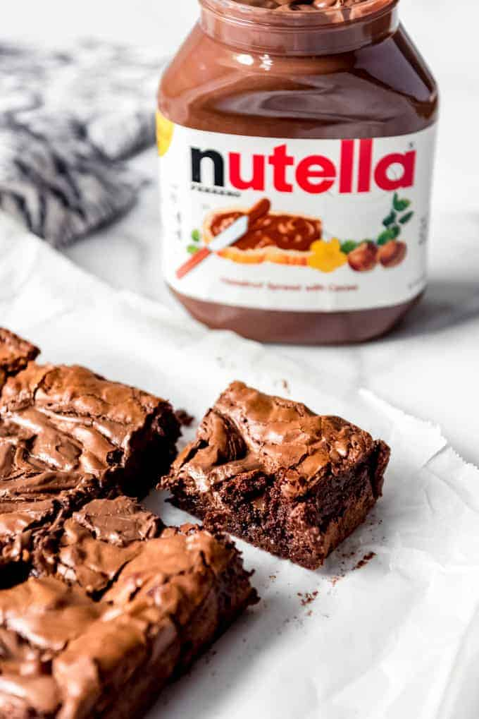 An image of homemade brownies in front of a Nutella jar.